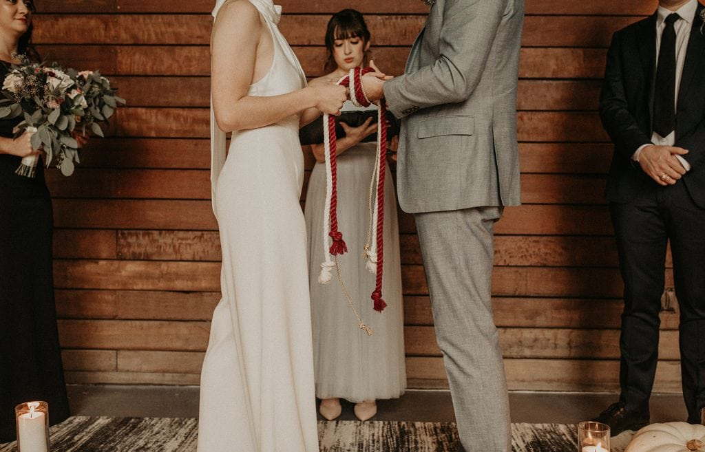 A bride and groom incorporate cultural traditions into their wedding ceremony by literally tying the knot around their hands, Photographed by Austin, Texas wedding photographer NIkk Nguyen