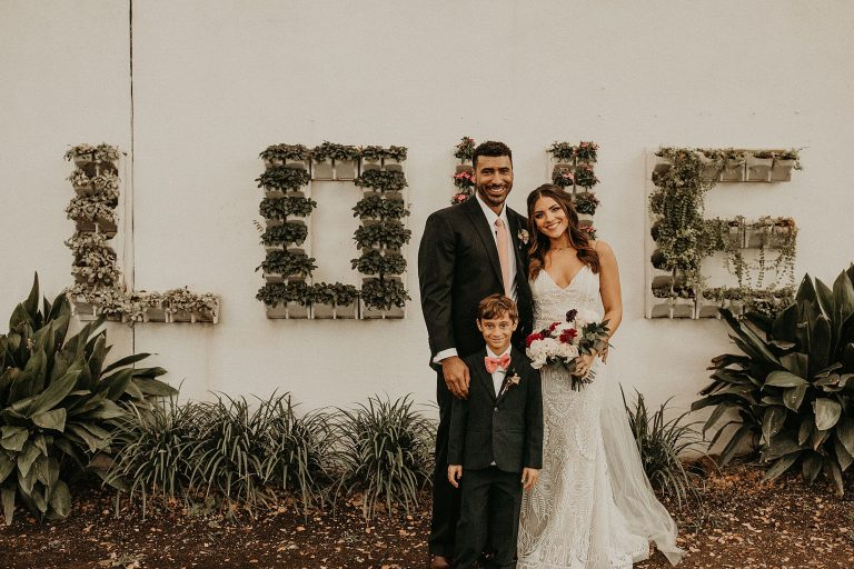 Bride and groom smile with their son for a portrait in front of a white wall with LOVE written in plants at