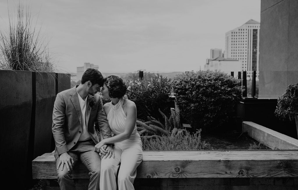 Black and white photo of newlywed couple sitting on wooden bench in front of some bushes. Couple is sitting next to eachother with their heads resting on eachother's as they smile and hold hands. Photographed in downtown Austin, Texas by Austin, TX wedding photographer Nikk Nguyen.
