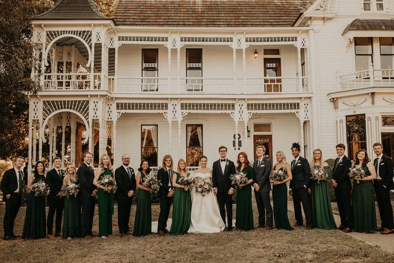 Bride and groom with wedding party in front of Victorian style home at Barr Mansion in Austin, Texas. Photograph by Austin, TX wedding photographer Nikk Nguyen.