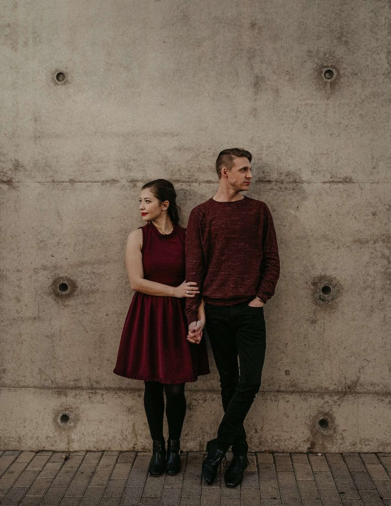 Couple holding hands as they stand with their backs against a concrete wall and their heads turned to opposite directions in downtown Austin, TX. Photographer by Austin, Texas wedding photographer Nikk Nguyen.