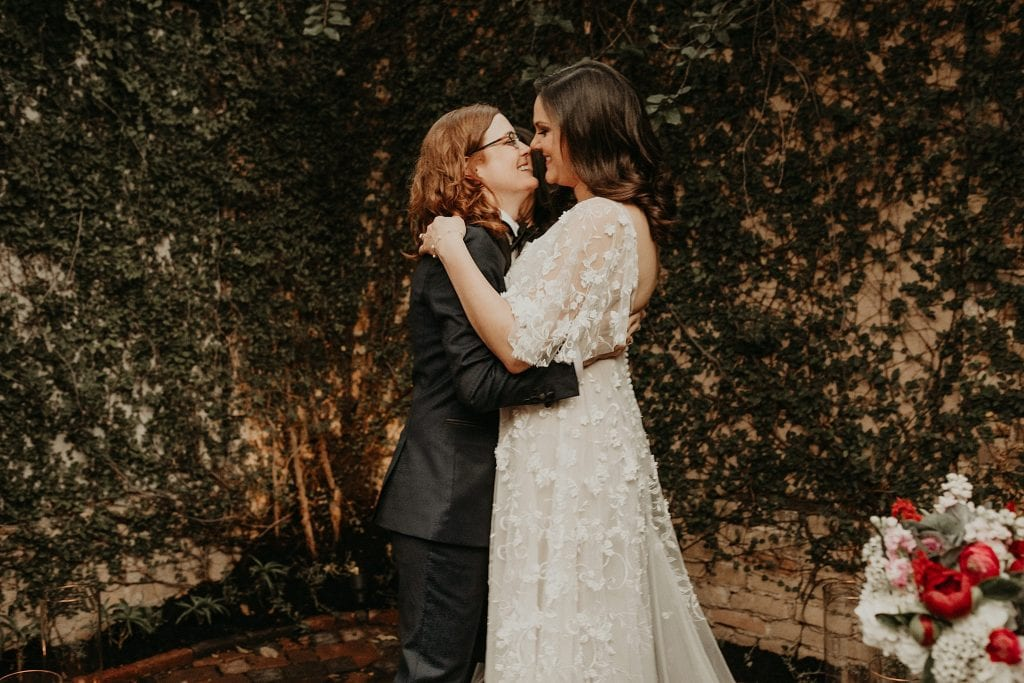 Brides embrace and smile at each other at the altar during ceremony at Justine's Secret House in Austin, Texas. Photograph by Austin, TX wedding photographer Nikk Nguyen.