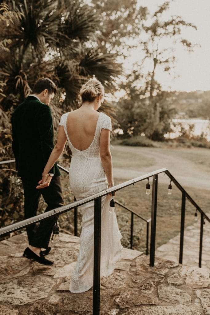 Bride and groom holding hands walking down stairs. Photographed by Austin, Texas wedding photographer Nikk Nguyen