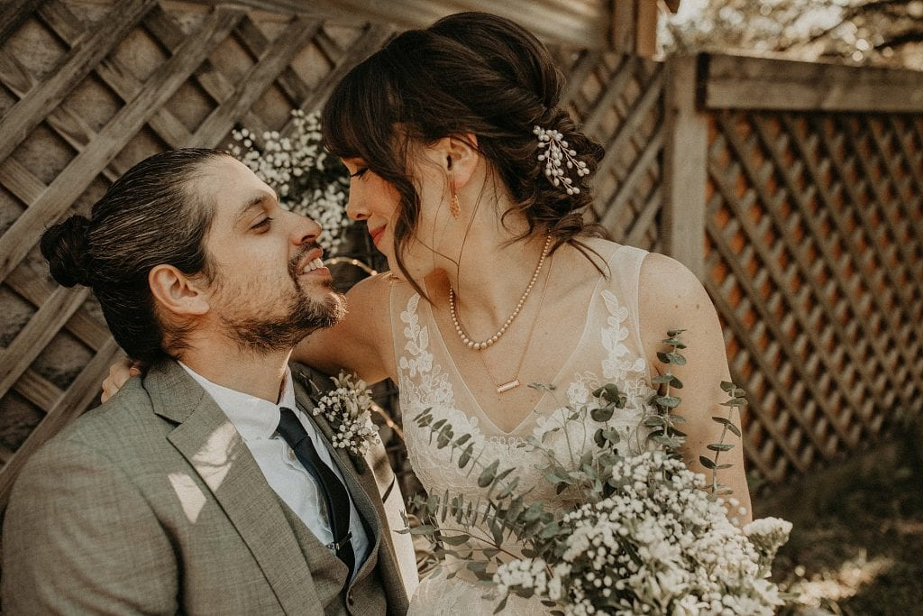 Close up of bride sitting on groom's lap as she wraps her arm around his shoulders and they face each other smiling during their House on the Hill wedding. Photograph at House on the Hill in Austin, Texas by Austin, TX wedding photographer Nikk Nguyen.