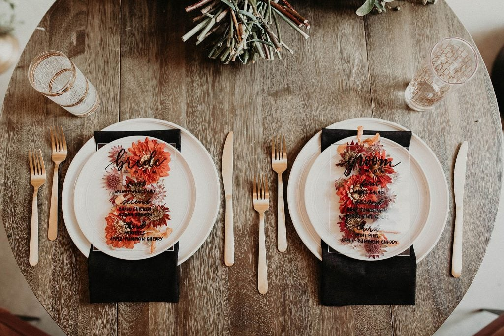 Wedding dinner menus displayed on a decorated table with forks, knives, and water glasses. Photographed by Austin, Texas wedding photographer Nikk Nguyen