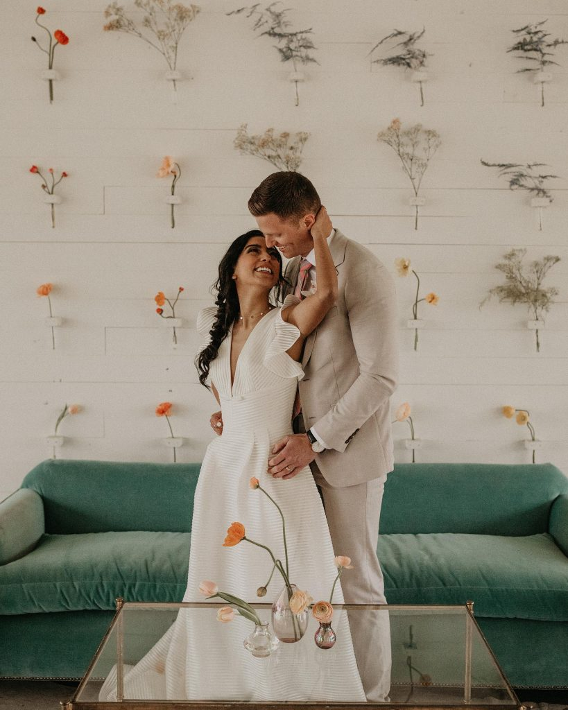 Groom embraces bride from behind as his hands rest on her hips and she tilts her head back to smile at him and embrace his face at Prospect House in Dripping Springs, Texas. Photographer by Austin, TX wedding photographer Nikk Nguyen at the Southern Love Workshop.