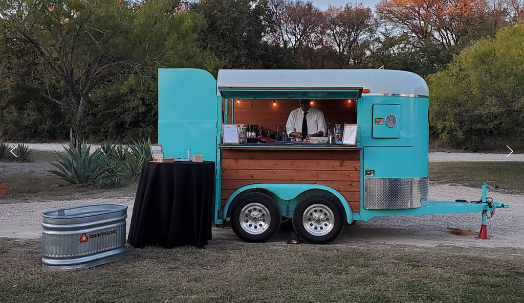 Party Pony Trailer stationed outside with a bartender working in the trailer serving drinks. Blog by Austin, Texas wedding photographer Nikk Nguyen