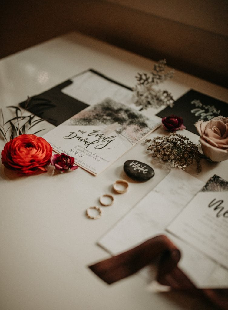 Wedding stationary and rings displayed on a decorated table with flowers and greenery. Photographed by Austin, Texas wedding photographer Nikk Nguyen