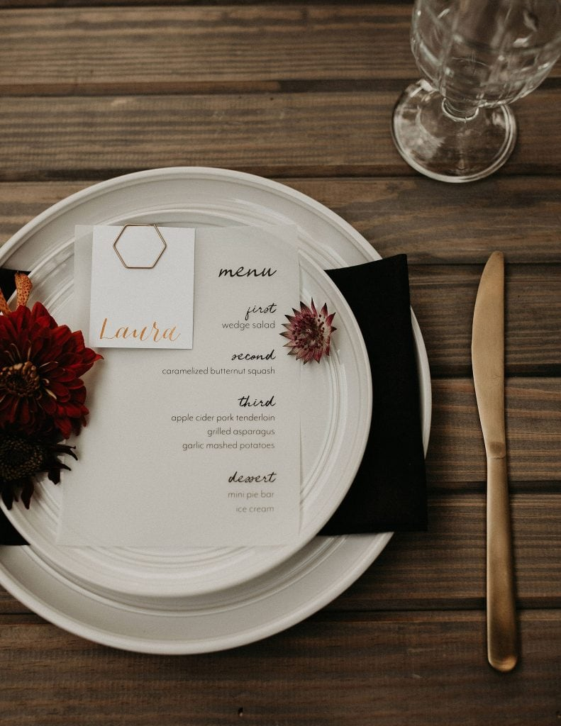 Wedding dinner menu displayed on a place setting, decorated with flowers. Photographed by Austin, Texas wedding photographer Nikk Nguyen