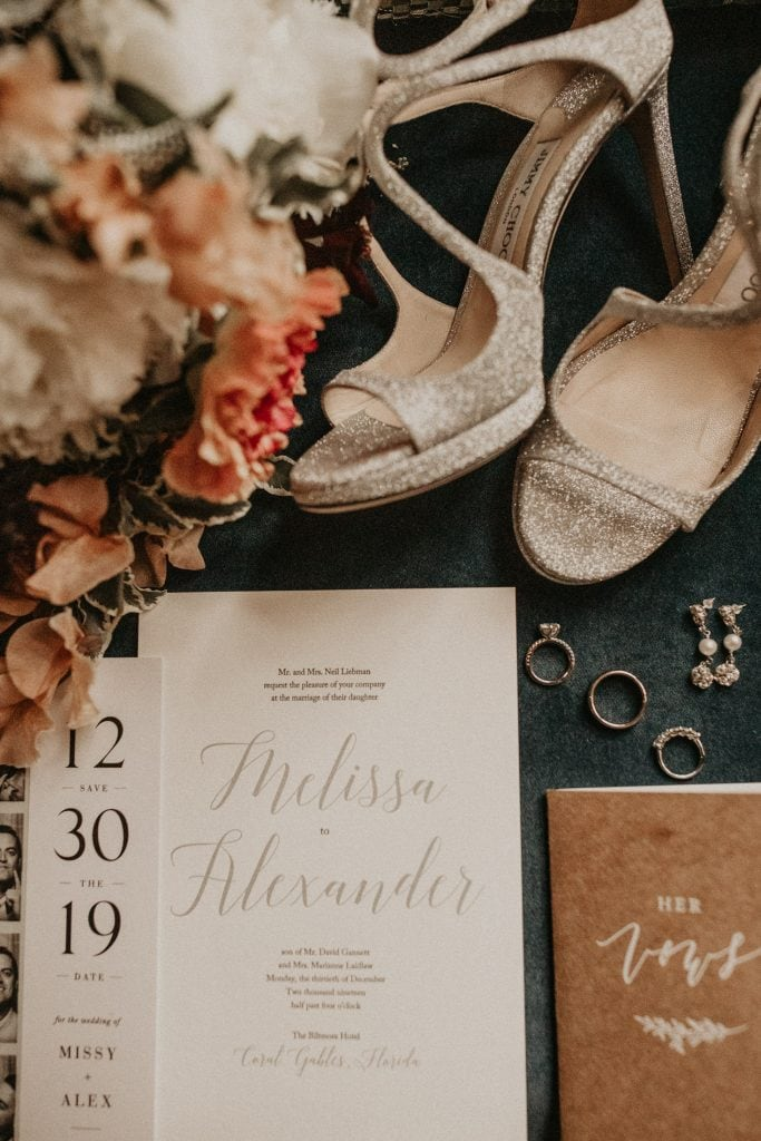 Flat-lay of save the date, wedding invitation, vows, engagement and wedding rings, earrings, and shoes. Photographed by Austin, Texas wedding photographer Nikk Nguyen