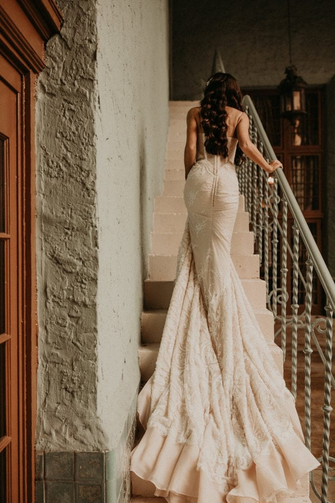 Bride walking up stairs in a lace wedding gown. Photographed by Austin, Texas wedding photographer Nikk Nguyen.