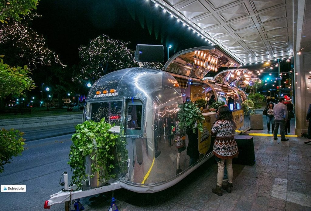 Sound cream airstream mobile DJ positioned outside at night on the street corner. Blog by Austin, Texas wedding photographer Nikk Nguyen