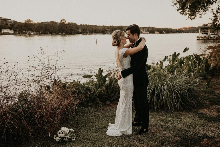 Bride and groom embrace and face each other on the banks of the Colorado River at The Contemporary Austin Laguna Gloria in Austin, Texas. Photograph by Austin, TX wedding photographer Nikk Nguyen.