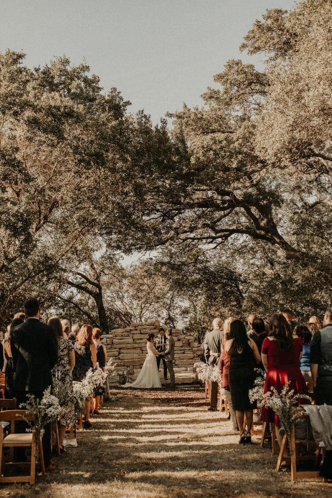 Bride and groom holding hands during outdoor wedding ceremony before the outbreak of Coronavirus (COVID-19). Photographed by Austin, Texas wedding photographer Nikk Nguyen