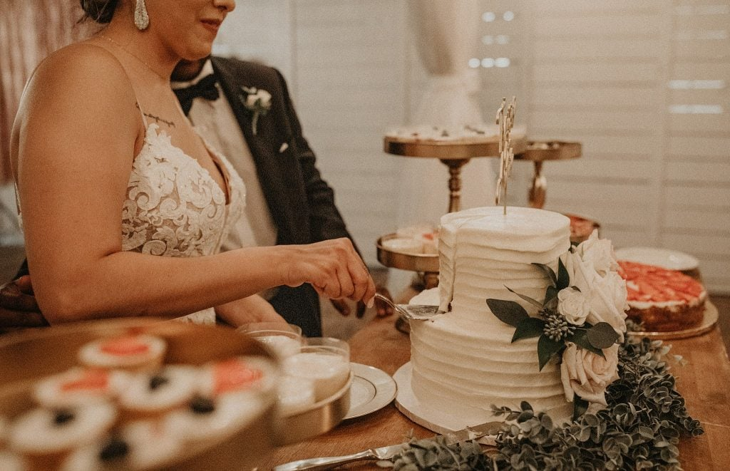 How to Choose a Wedding Cake Designer for Your Big Day. Bride cutting a slice of her wedding cake standing beside her groom at the dessert table. Photographed by Austin, Texas wedding photographer Nikk Nguyen