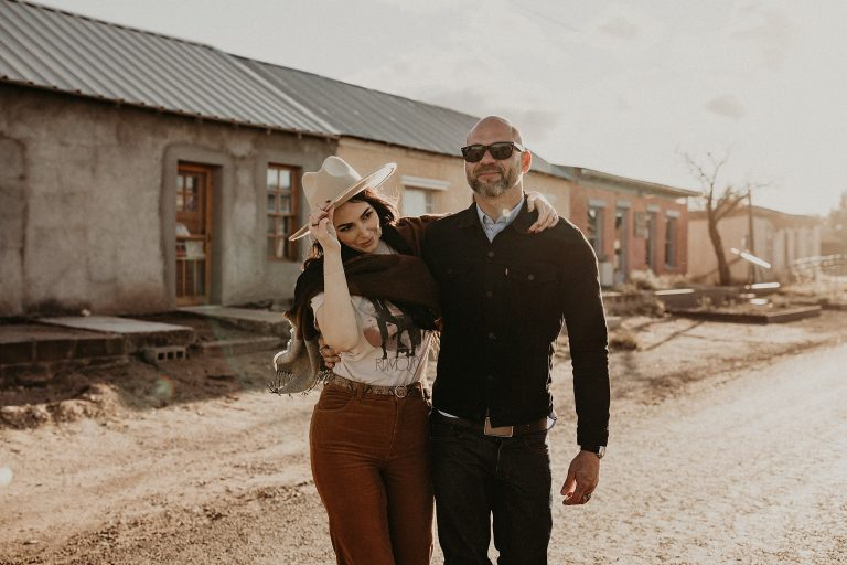 Engaged couple walking with their arms wrapped around each other as future groom looks causally into the distance and bride tilts her head and touches her hat. Photograph taken in Marfa, Texas by Austin, TX wedding photographer Nikk Nguyen.