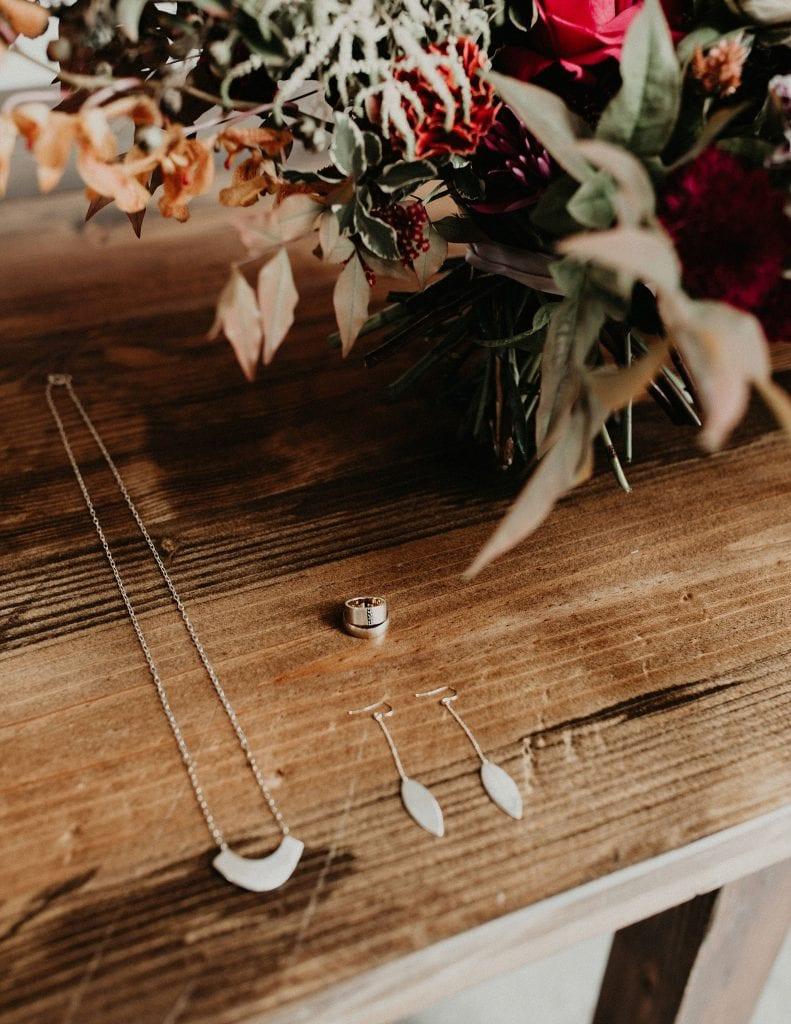 Shaesby wedding jewelry sits on a table next to a wedding bouquet during a wedding styled shoot in Austin Texas by wedding photographer Nikk Nguyen.