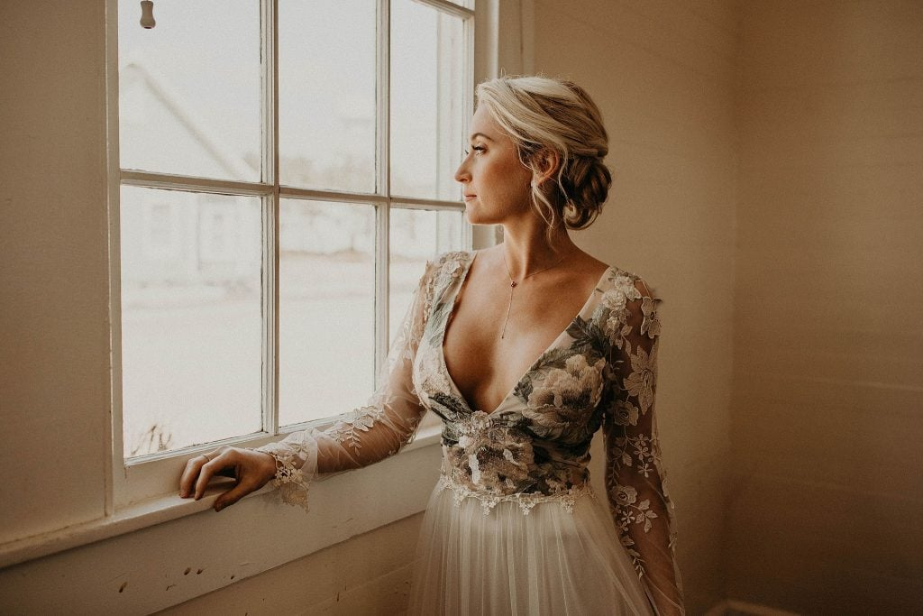 Bride wearing handcrafted, artisan wedding jewelry by Shaesby on her wedding day looking out a window. Photographed by Austin, Texas wedding photographer Nikk Nguyen