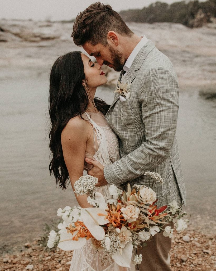 Bride and groom embrace during a vagabond wedding shoot as their noses touch and bride holds bouquet at Pedernales Falls State Park in Johnson City, TX. Photograph by Austin, Texas wedding photographer Nikk Nguyen.