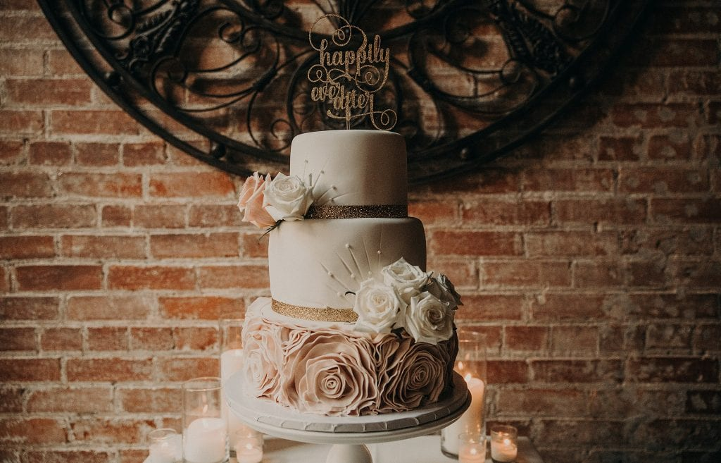 "How to Choose a Wedding Cake Designer for Your Big Day. Three-tiered wedding cake with ""Happily Ever After"" on top, decorated with pink and white florals. Photographed by Austin, Texas wedding photographer Nikk Nguyen"