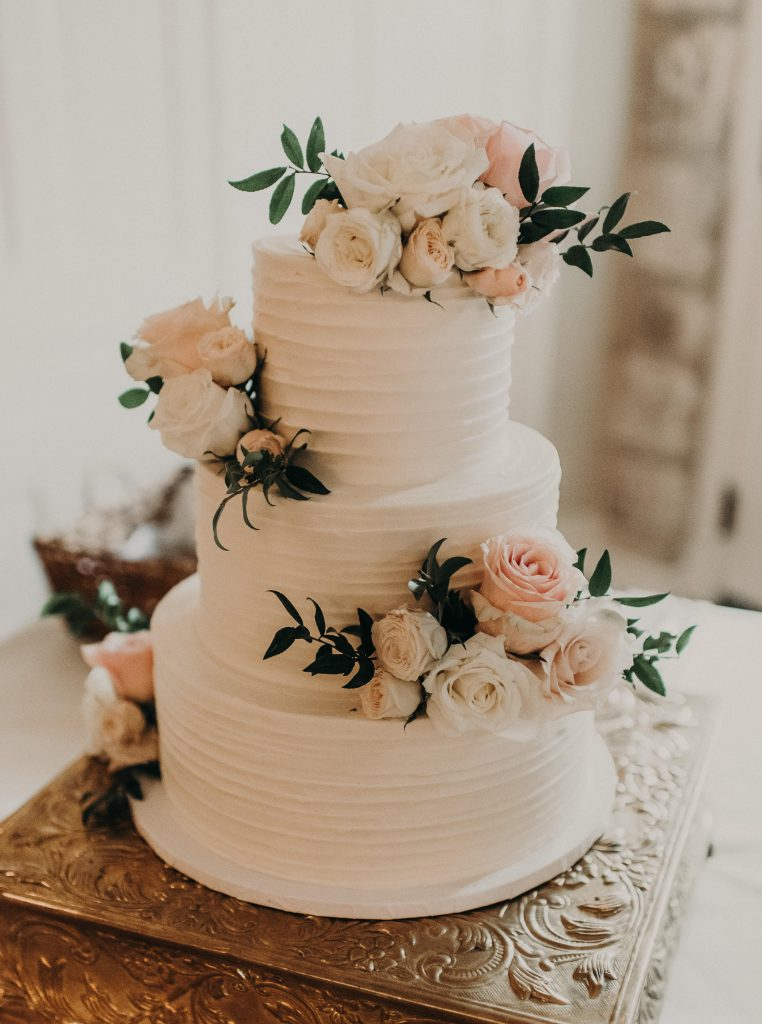 How to Choose a Wedding Cake Designer for Your Big Day. Three tiered wedding cake with peach and white flowers for garnish. Photographed by Austin, Texas wedding photographer Nikk Nguyen