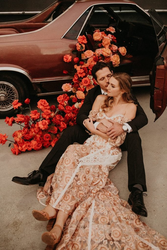 Bride sits cuddled in front of groom as he kisses her cheek during the final shoot of The Southern Love workshop at 800 Congress in Austin, Texas. Couple is sitting in front of a bouquet of bright red and pink roses and ranunculus' overflowing out of the passenger seat of a vintage El Camino. Photograph by Austin, TX wedding photographer Nikk Nguyen