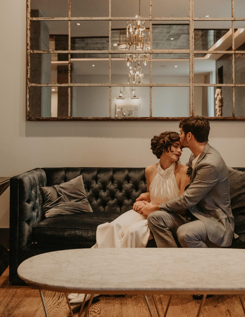Bride and groom sitting on a chair in a hotel with groom kissing bride's forehead. Photographed by Austin, Texas wedding photographer Nikk Nguyen
