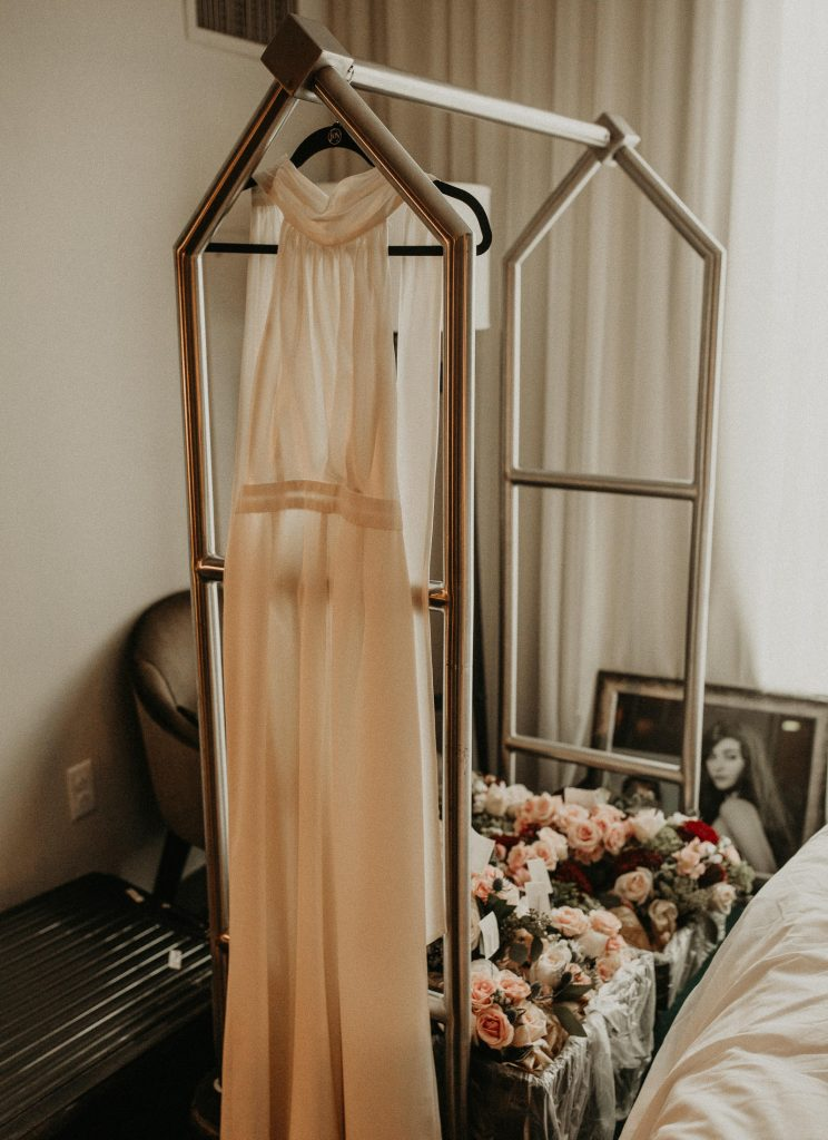Wedding dress hanging from a valet cart with a box of florals and photos. Photographed by Austin, Texas wedding photographer Nikk Nguyen