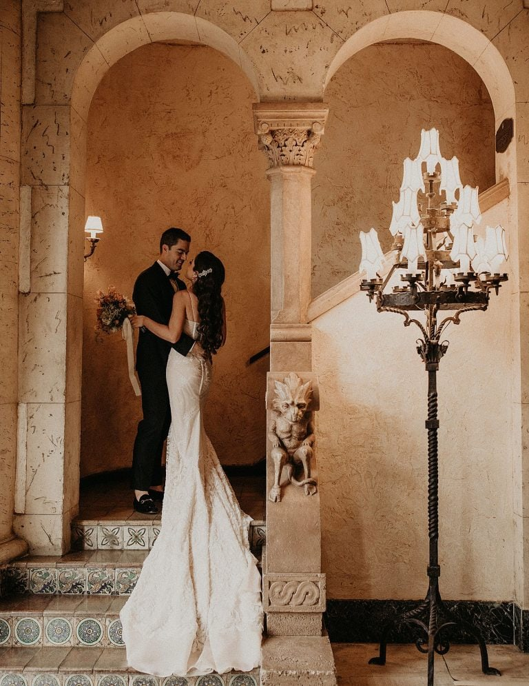 Bride and groom embrace while standing in the threshold of a grand Mediterranean staircase at Biltmore Hotel Miami Wedding in Coral Gables, Florida. Photograph by Austin, Texas wedding photographer Nikk Nguyen.