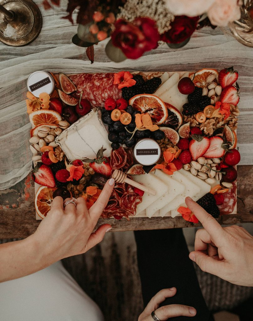 Hands of bride and groom point to the items on a cheese, nut, and fruit grazing table provided by Grazeology in Austin, Texas. Photograph by Austin, TX wedding photographer Nikk Nguyen to promote how to have an epic reception with these Austin, Texas wedding caterers.