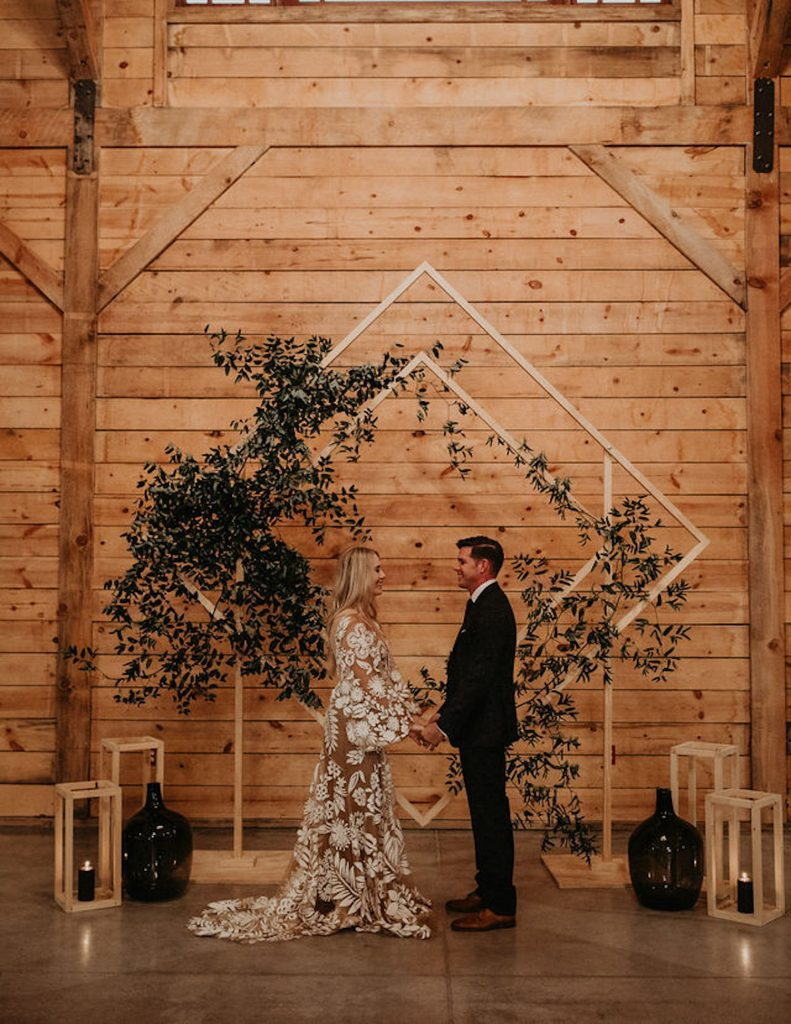 Bride and groom stand at the altar holding hands surrounded by rentals and decorations from Bee Lavish, an Austin based rental company. Image by Austin, Texas wedding photographer Nikk Nguyen.