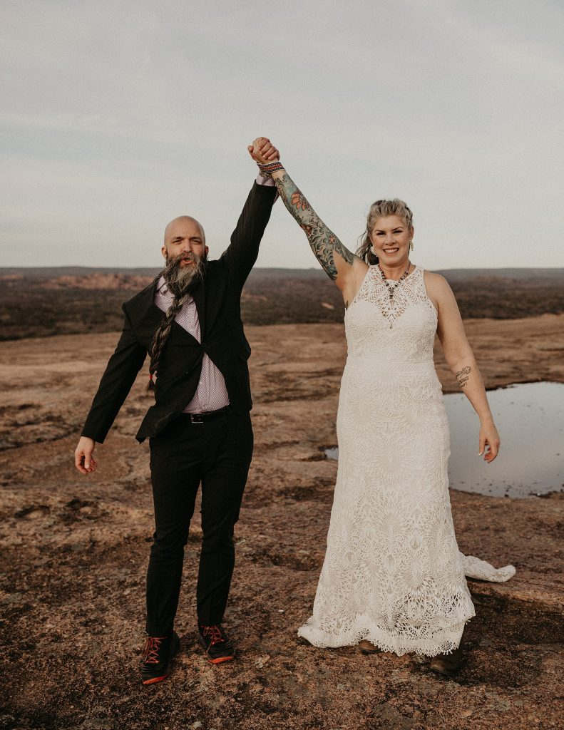 Bride and groom stand at the top of a summit during their Enchanted Rock Elopement in Fredericksburg, Texas with their held hands raised high. Photograph by Austin, TX wedding photographer Nikk Nguyen.