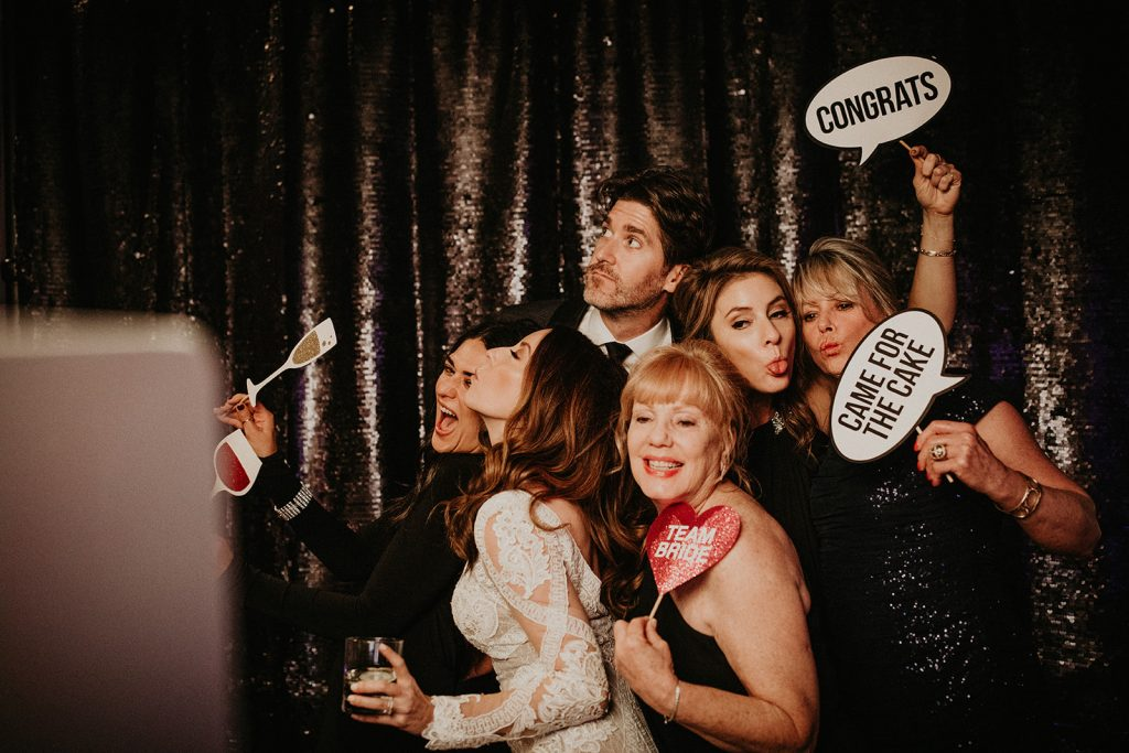 Bride and groom pose with their wedding guests at the photo booth provided by Austin based Oh Happy Day. Image by Austin, TX wedding photographer Nikk Nguyen.