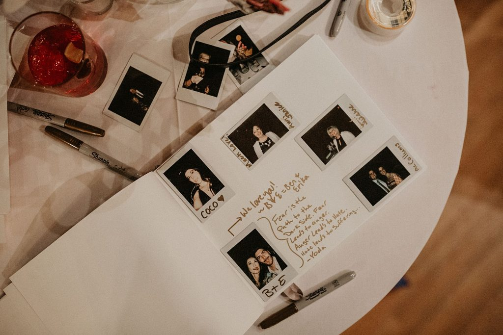 A overhead shot of a wedding guestbook filled with photos from Oh Happy Day Booth, an Austin, TX based company that offers photo booth rentals. Photograph by Austin, Texas wedding photographer Nikk Nguyen.