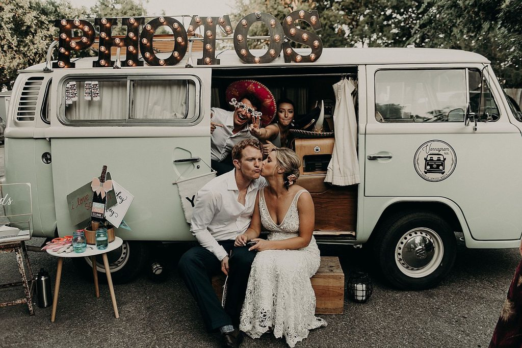 Bride kisses groom on the cheek in front of VW van photo booth from Vannagram & Co, an Austin based company. Image by Austin, TX wedding photographer Nikk Nguyen.