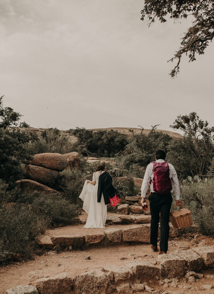 A bride and groom hike in Enchanted Rock State Park outside of Austin, Texas as an example of what to do when your wedding is postponed. Photograph by Austin, TX wedding photographer Nikk Nguyen.