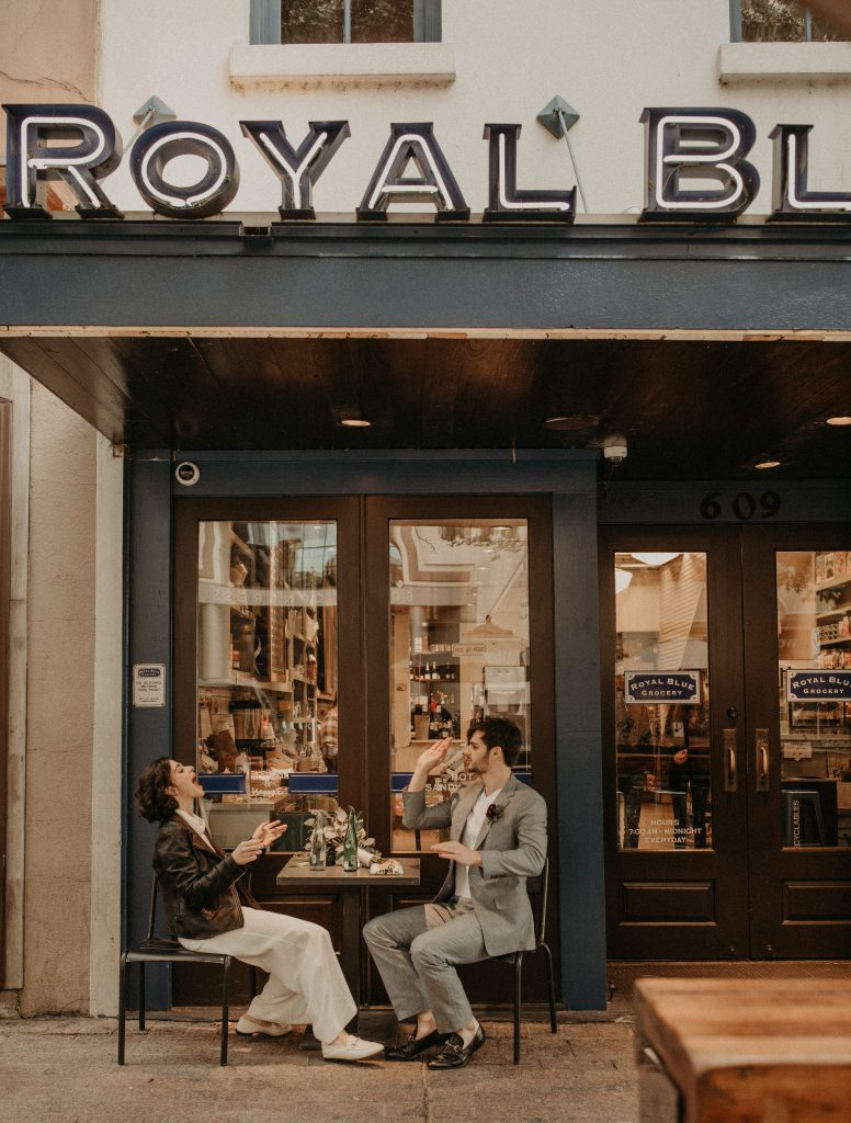 A bride and groom sit at a table outside a small cafe in downtown Austin, Texas and groom throws food into bride's mouth as an example of something fun to do when your wedding is postponed. Photograph by Austin, TX wedding photographer Nikk Nguyen.