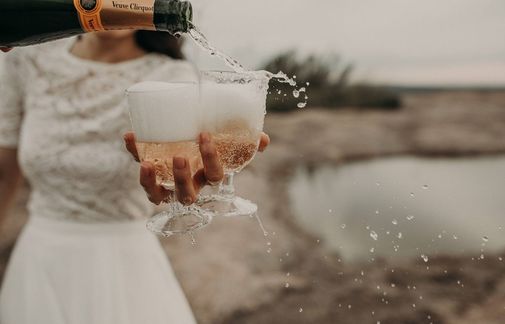 A photo by Austin, TX wedding photographer Nikk Nguyen, of champagne being poured into glasses held by a bride at Enchanted Rock State Park outside of Austin, Texas as an example of how to celebrate your wedding if it is postponed.