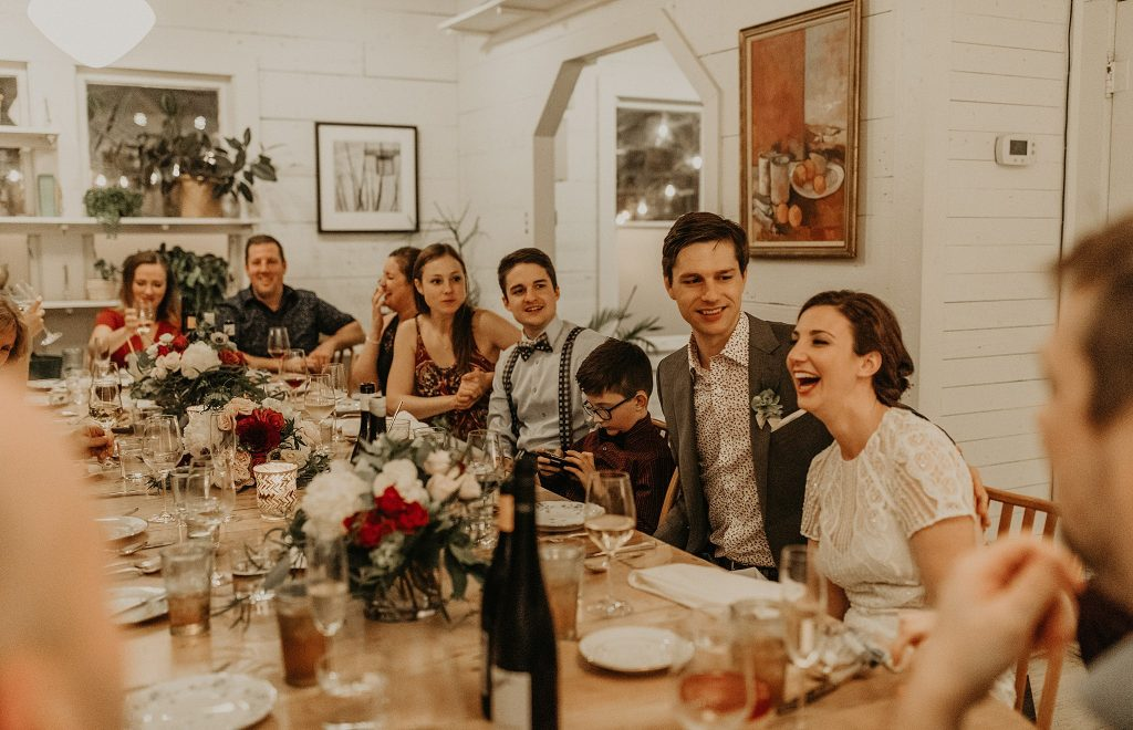 Bride and groom smile while sitting at a family-style table with their friends and family during their micro wedding in Austin, Texas. Photograph by Austin, TX wedding photographer Nikk Nguyen.