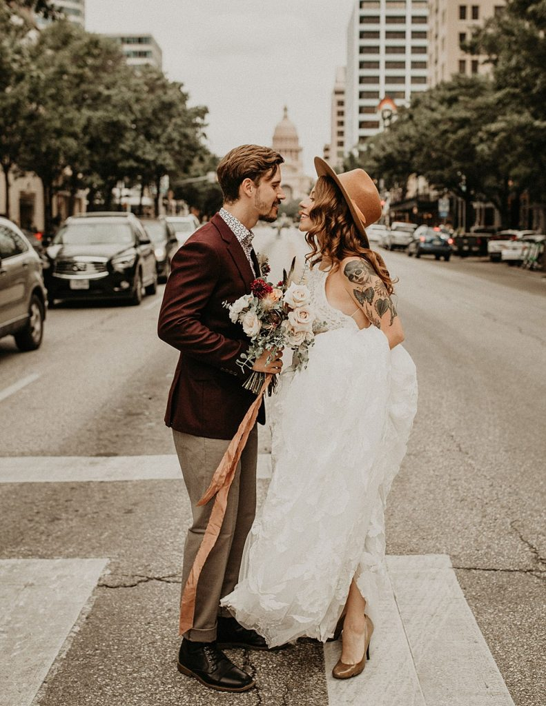 """Bride and groom smile at each other while standing in the middle of the street in downtown Austin, Texas during their elopement. Photograph by Austin, TX wedding photographer Nikk Nguyen as an example of an answer to the question """"what is an elopement?"""""""