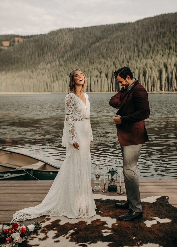 """A bride laughs as the groom gets the rings out of his pocket as they stands at the altar near the river at Piney River Ranch in Vail, Colorado during their elopement wedding. Photograph by Nikk Nguyen, an Austin, Texas wedding photographer as an example of the answer to the question """"what is an elopement?"""""""