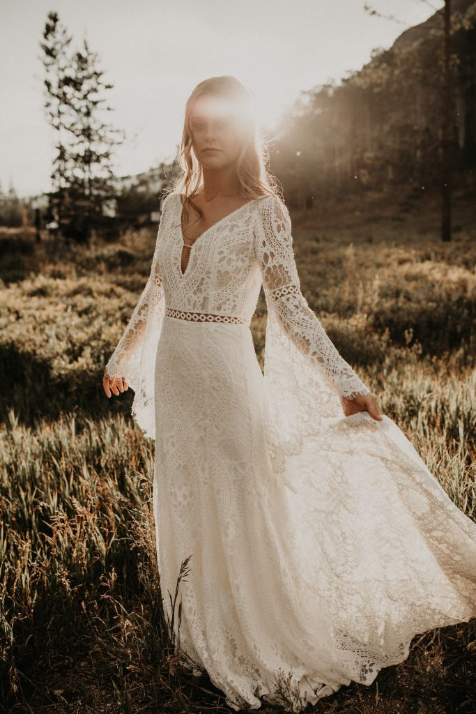 A bride in a boho wedding dress in the fields of Vail, Colorado as an example of a wedding dress found at a Texas Bridal Boutique. Image by Austin, TX wedding photographer Nikk Nguyen.