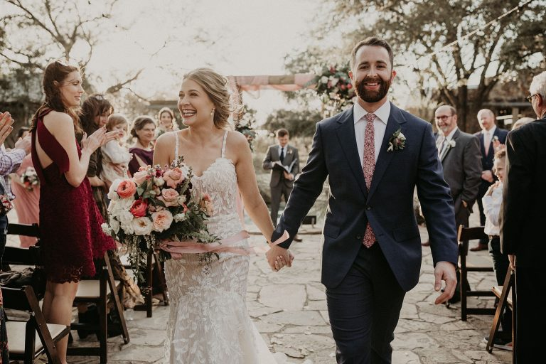 Bride and groom smile as they hold hands and walk down the aisle after the ceremony of their Lady Bird Johnson Wildflower Wedding in Austin, Texas photographed by Austin, TX wedding photographer Nikk Nguyen.