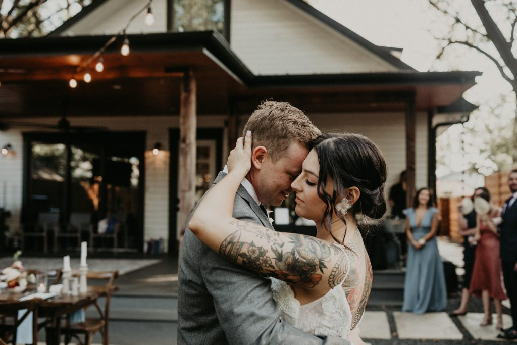 Bride and groom embrace during their first dance at their micro wedding venue. Image by Austin, Texas wedding photographer Nikk Nguyen.