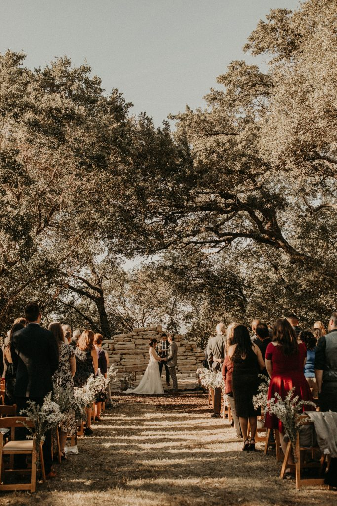 Bride and groom hold hands at the altar at House on the Hill, their micro wedding venue. Image by Austin, Texas wedding photographer Nikk Nguyen.
