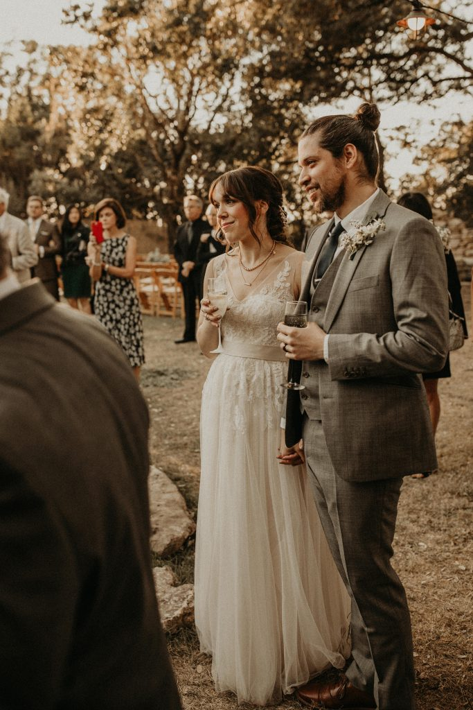 Bride and groom smile while hearing a speech at House on the Hill. Image by Austin, Texas wedding photographer Nikk Nguyen.
