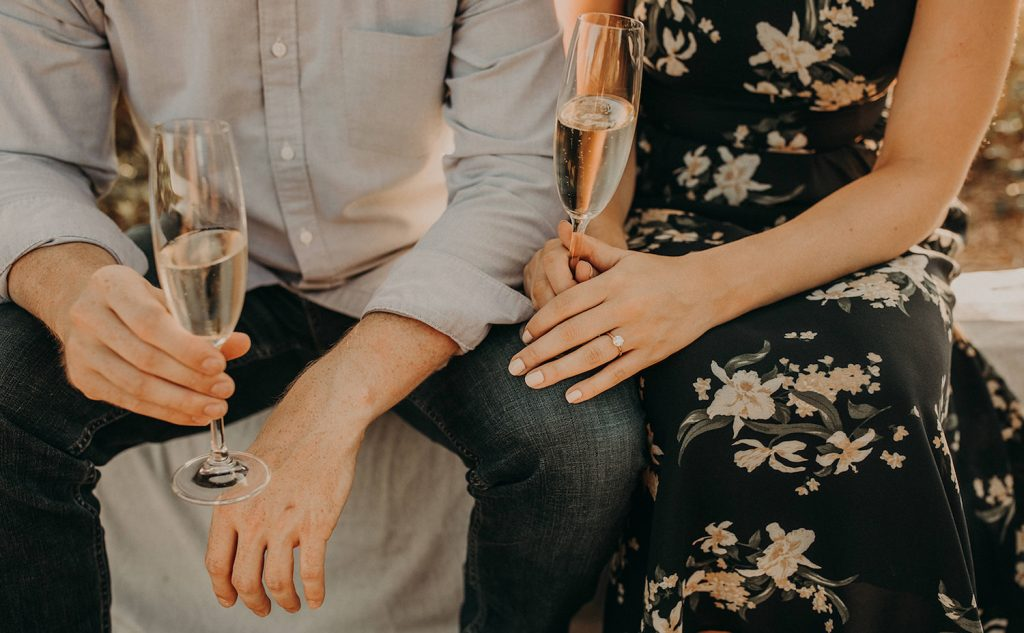 A close up of a newly engaged couple drinking champagne as they talk about what an engagement party is and how to plan one. Image by Austin, Texas wedding photographer Nikk Nguyen.