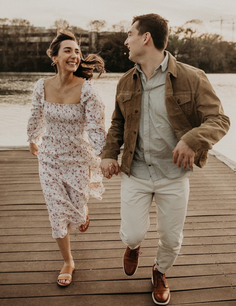 A newly engaged couple smiles at each other as they run off a dock in downtown Austin, Texas and decide what is an engagement party and how to celebrate it. Image by Austin, TX wedding photographer Nikk Nguyen.