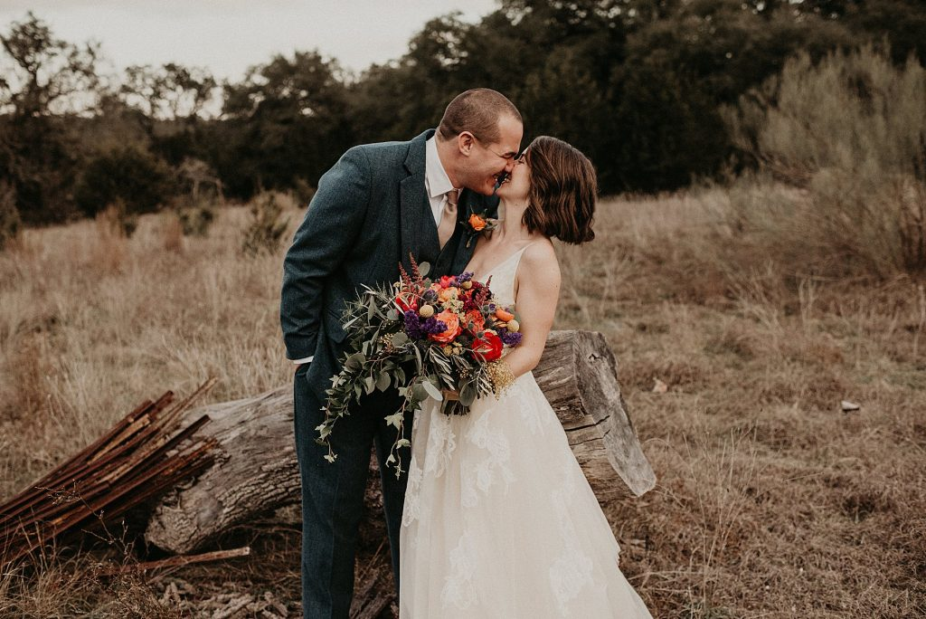 Bride and groom embrace with their faces nuzzles together as they smile about their Wedding at Sacred Oaks at Camp Lucy in Dripping Springs, Texas. Photograph by Austin, TX wedding photographer Nikk Nguyen.