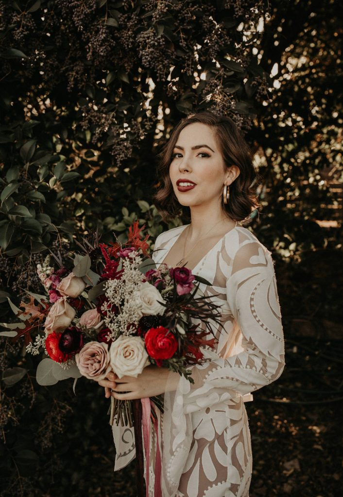 A bride holding a bouquet in her bohemian wedding dress from Unbridaled, an Austin, Texas bridal boutique. Image by Nikk Nguyen, an Austin, TX wedding photographer.